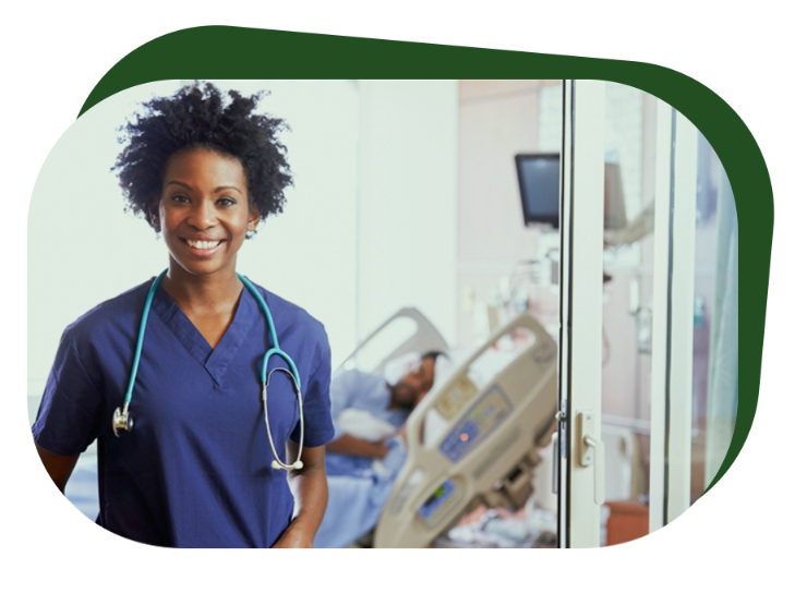 A nursing program student smiles while wearing a stethoscope and scrubs in a hospital room