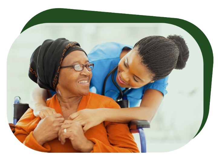 A female nurse smiles and hugs an elderly female patient in a wheelchair